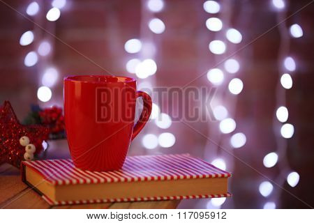 A red cup and a book on lighted wall background