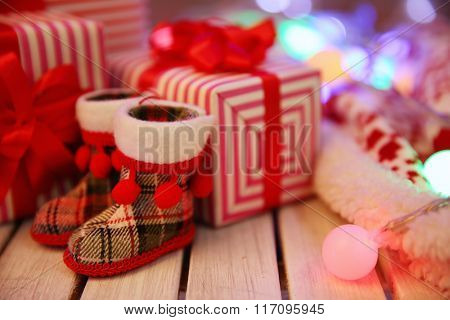Christmas gift boxes, boots and lights on the wooden table