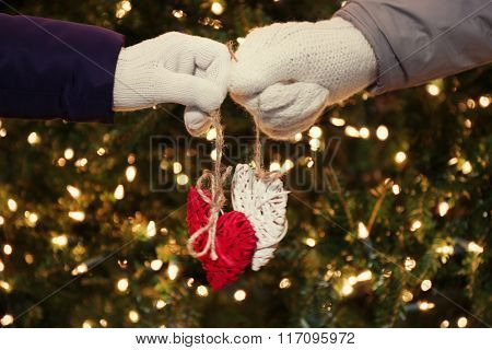 Hands holding tiny hearts on lighted background