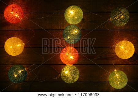 Electric Christmas garland on wooden background, closeup