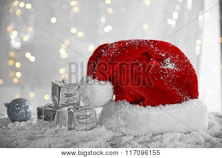 Santa Claus hat with bauble and gift boxes on a snowy table over glitter background