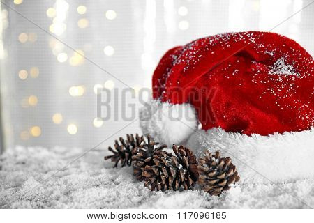 Santa Claus hat with cones on a snowy table over glitter background