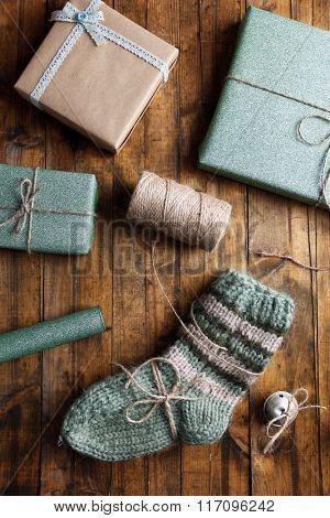 Pair of knitted socks with wrapped gifts for Christmas on wooden table