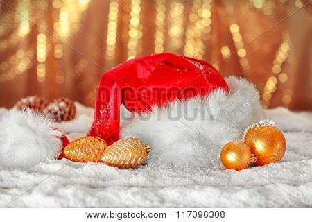 Santa Claus red hat with Christmas decorations on the artificial snow against golden background, close up