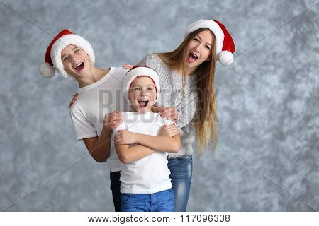 Boys and girl in Santa hats on grey background
