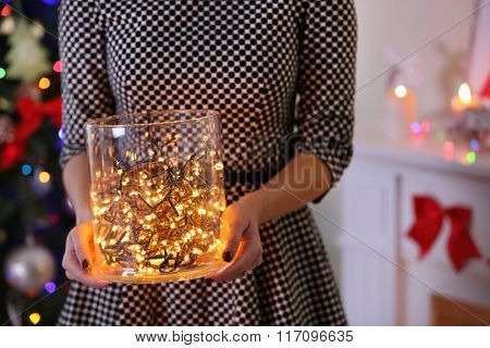 Jar with garland in woman hands