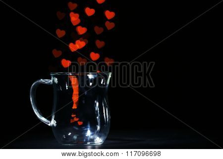 Miracle of love from glass cup on black background