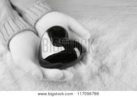 Hands in warm white gloves holding black heart on snowy background