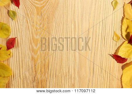 Autumn leaves on light wooden background