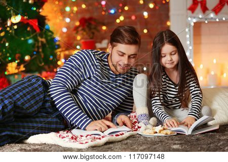 Older brother with little sister reading books and eating cookies in Christmas living room