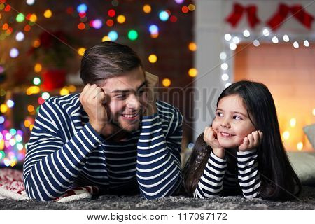 Older brother with little sister lying on a carpet in Christmas living room