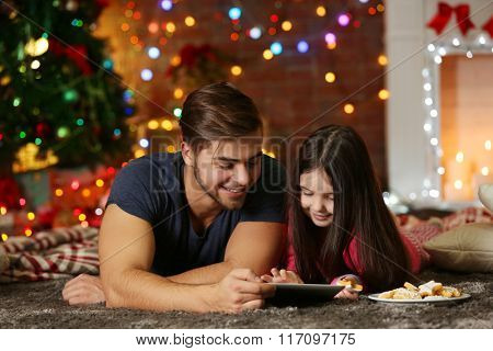 Older brother with little sister using tablet and eating cookies in Christmas living room