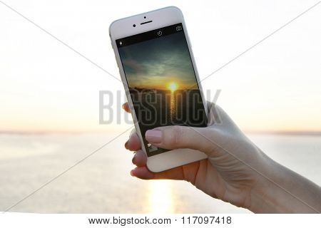 Female hand holding smart phone and taking photo of sunset