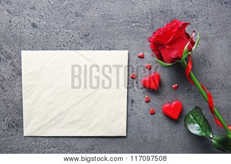Blank present Valentine card with beautiful rose on grey textured background