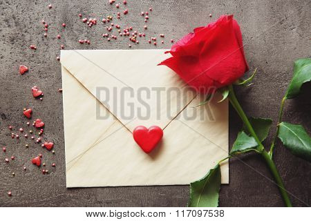 Blank present present envelope with small hearts and red rose on grey textured background