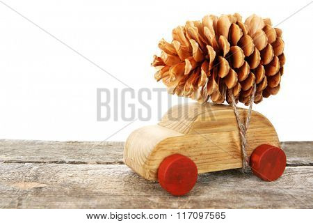 Wooden toy car with pine cone on a table over white background
