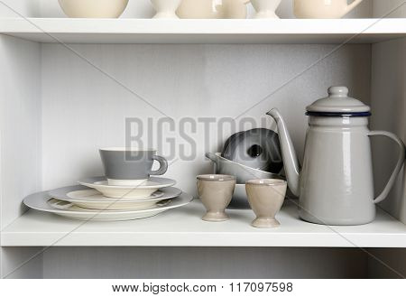 Tableware on shelves in the kitchen cupboard