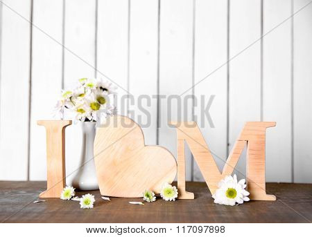 Wooden letters with heart and flowers on white wall background
