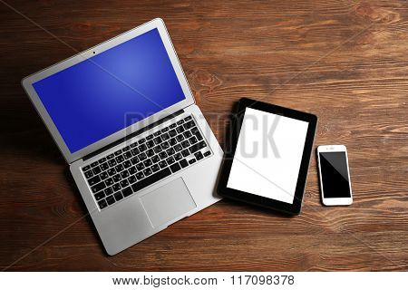 Modern laptop, mobile phone and tablet on wooden background