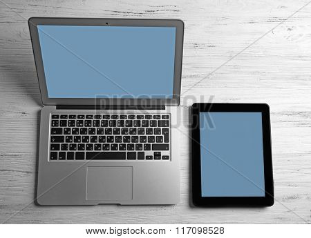 Modern laptop and tablet on white wooden background