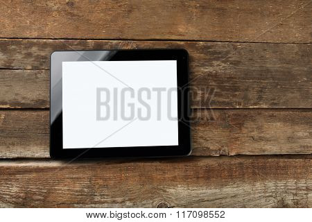 A black modern tablet on the wooden background