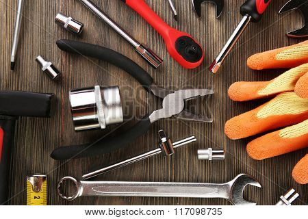 Different kinds of tools on wooden background, top view
