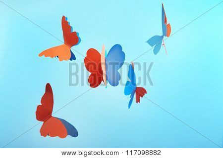 Paper butterflies on blue background