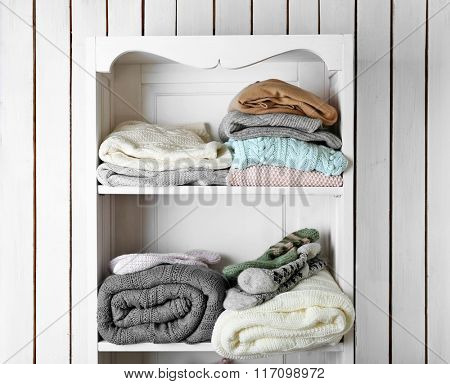 Knitting clothes on wooden shelf