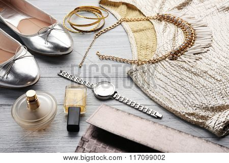 Composition of elegant woman's fashion look on wooden background, close up