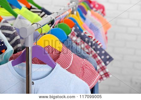 Children clothes on hangers in a room