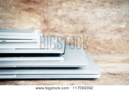 Pile of different modern electronics gadgets on old wooden background