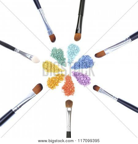 Different makeup brushes and eye shadows isolated on white