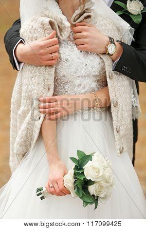 Thoughtful groom hugging bride