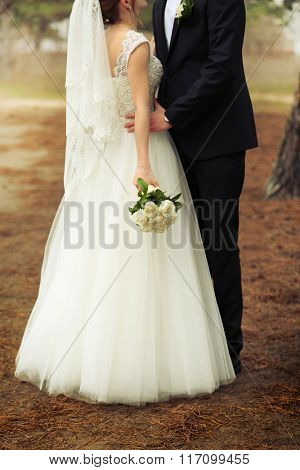 Happy bride and groom hugging on a forest background
