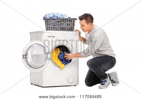 Young man putting clothes in a washing machine isolated on white background