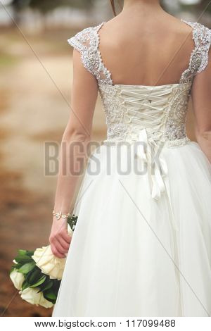 Beautiful bride with a bouquet standing back