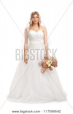 Full length portrait of a young sad bride holding a teddy bear and looking at the camera isolated on white background