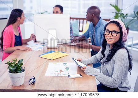 Cheerful businesswoman holding digital tablet while sitting with colleagues in office