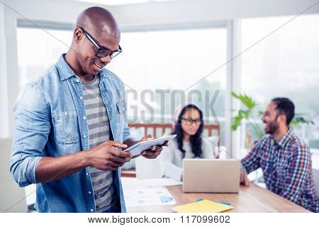 Happy young businessman using digital tablet while standing at office