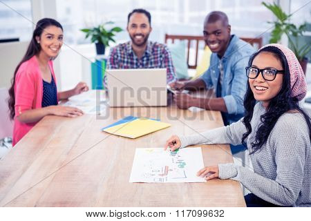 Portrait of happy business people at desk in office