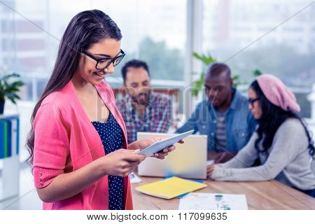 Happy young businesswoman using digital tablet while standing at office