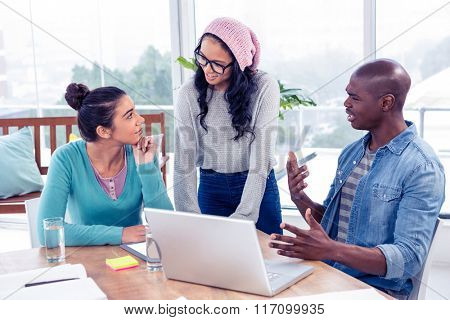 Business people discussing over laptop in creative office