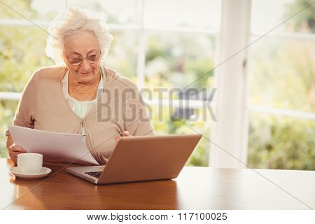 Senior woman dealing with documents while using laptop at home