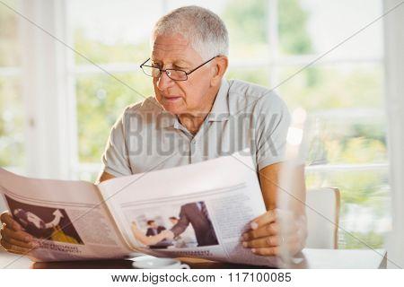 Focused senior man reading newspaper at home
