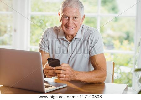 Senior man using his laptop and smartphone at home