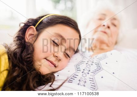 Relaxed granddaughter and grandmother napping on sofa