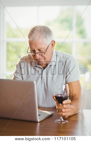 Focused senior man using laptop and drinking wine at home