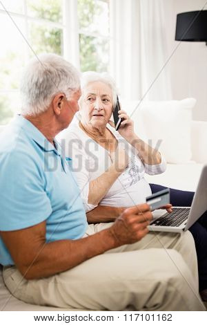 Smiling senior couple using laptop and smartphone at home