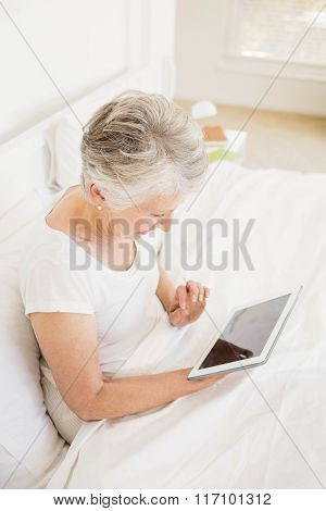 Smiling woman using tablet sitting on the bed