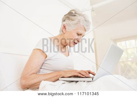 Mature woman using laptop sitting on bed